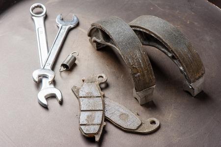 zapatos de seguridad: desgastado pastillas de freno de la motocicleta y zapatos de quiebre Foto de archivo