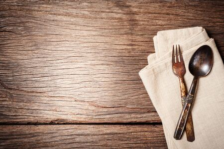 dinning: dinning table background with old brass spoon and fork Stock Photo