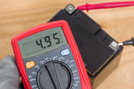 electrician using the digital multimeter to check the motorcycles battery Stock Photo