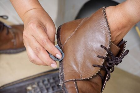 sanding the shoe before apply adhesive, shoe repair