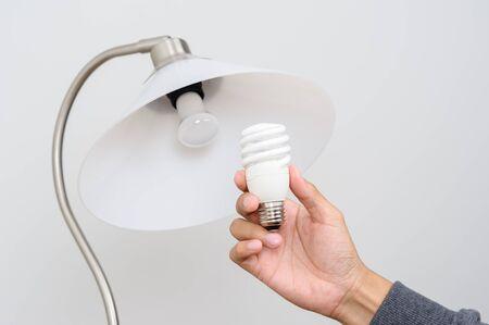 electric bulb: closeup hand changing an electric light bulb Stock Photo
