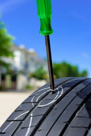 unscrew from car tyre, damaged car tyre