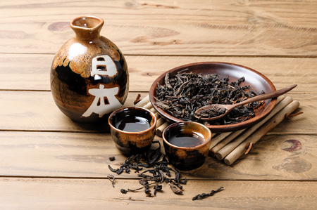 the classic brown japanese tea set on wooden table, with the word meaning Japan on the jar. Stock Photo