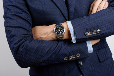 Closeup luxury wristwatch on the wrist of businessman in navy blue suit