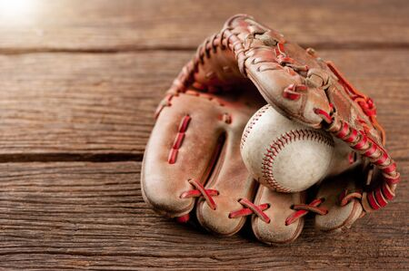 old vintage baseball glove with the baseball held in the palm on wooden background (Shallow depth of field) Stock Photo