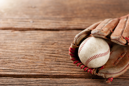 shallow: old vintage baseball glove with the baseball held in the palm on wooden background (Shallow depth of field) Stock Photo