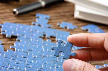 playing blue jigsaw puzzle game on wooden table
