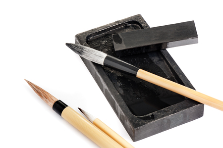 inkstone, inkstick and traditional writing brush isolated on white background