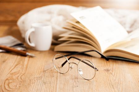 クローズ アップ ラウンド木製の机、フィールドの浅い深さの上の眼鏡のフレーム スタイル
