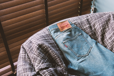 levi: BANGKOK, THAILAND - JANUARY 13, 2017: LEVIS jeans on sofa. LEVIS is a brand name of Levi Strauss and Co, founded in 1853.