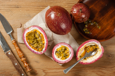 Fresh passion fruit on wooden background. Passion fruit contains many small black seeds covered with the fruits flesh. Stock Photo