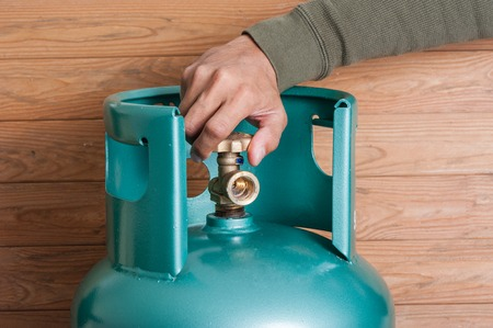 Closeup mans hand operating valve of LPG cylinder for cooking