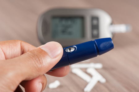 closeup blood lancet device, used for blood testing. Blood glucose meter for diabetics in background. Stock Photo