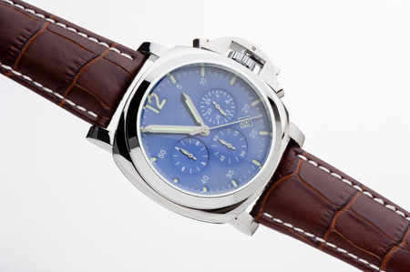 cronógrafo: luxury fashion watch with blue dial and brown crocodile grain leather watch band on white background