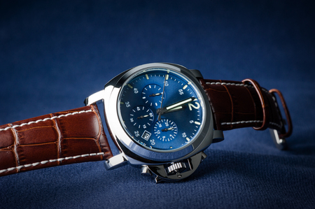 luxury fashion watch with blue dial and brown crocodile grain leather watch band