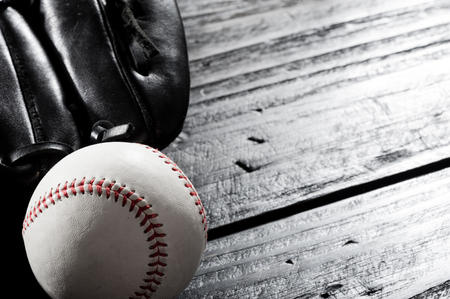 closeup baseball glove and baseball on wood board, dark theme, sport concept