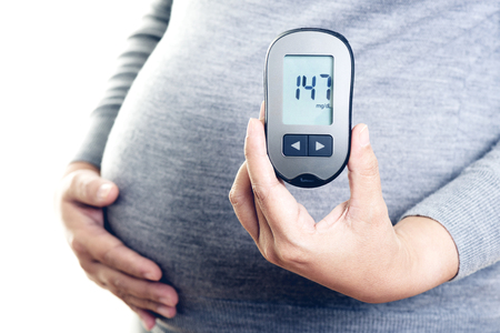 Pregnant woman checking blood sugar level with blood glucose meter. Gestational diabetes.