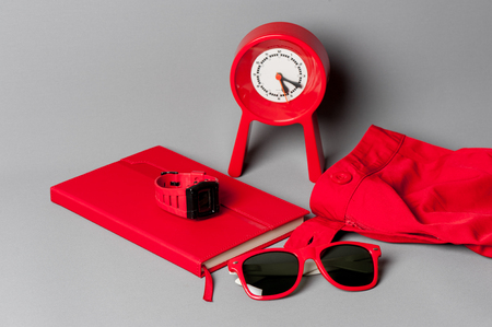 red objects, sunglasses, notebook, clock, watch, closeup at red plastic sunglasses Stock Photo