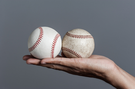 closeup baseball in mans hand, isolated over background