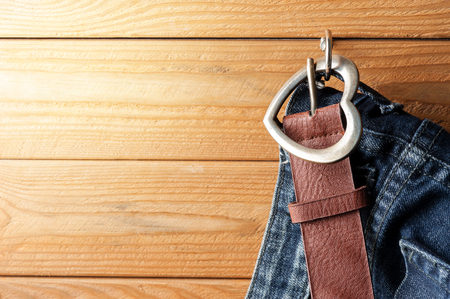 closeup brown leather woman belt with metal heart shaped belt buckle on wooden board Stock Photo