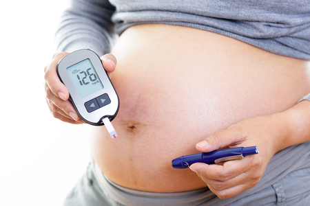 gestational: Pregnant woman checking blood sugar level with blood glucose meter. Gestational diabetes.