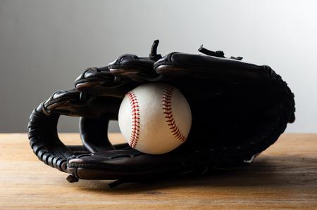 chocolate brown baseball glove with baseball on wood board