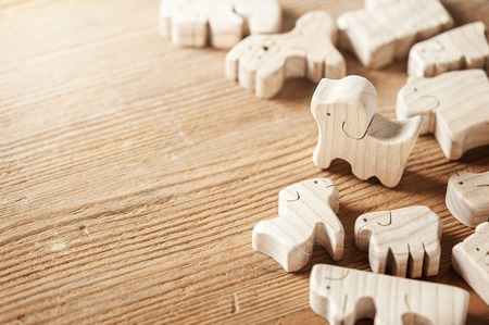 toys background, cute wooden toy animal on wood board, tiny toys and shallow depth of field