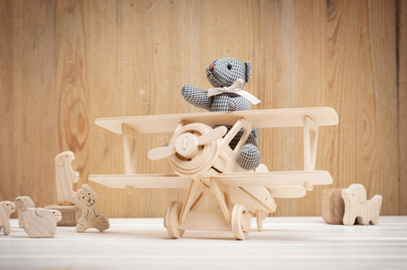 Cute teddy bear on wooden background with wooden baby toys