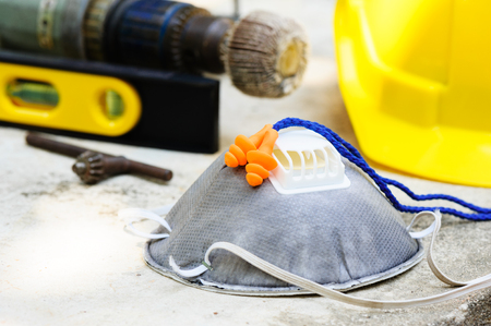 Orange reusable ear plugs in construction site, personal safety equipment concept. Outdoor shooting and shallow depth of field.