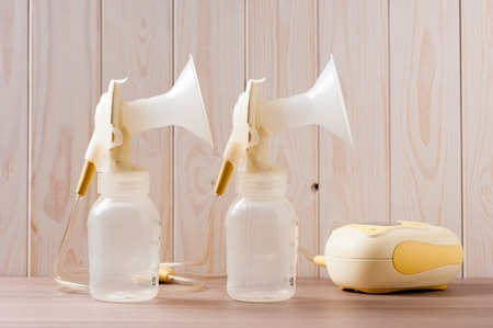 double Breast pump with blank baby bottle on wood background