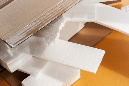 Closeup white polystyrene foam in parcel box. Polystyrene foam is cushioning material in packaging, material for craft applications and other.