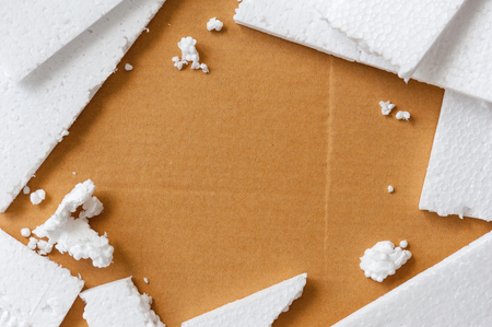 Closeup white polystyrene foam on the cardboard. Polystyrene foam is cushioning material in packaging, material for craft applications and other.