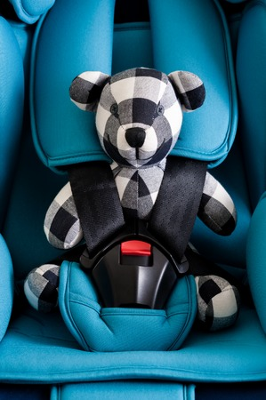 teddy bear in blue child safety seat, seat designed specifically to protect children from injury or death during collisions. Stock Photo