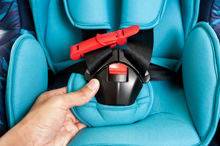 closeup details of blue child safety seat, seat designed specifically to protect children from injury or death during collisions.