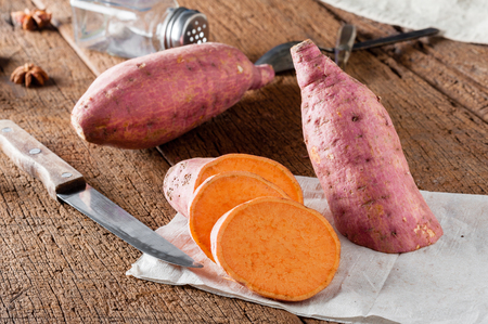 raw sweet potato over old wood background  Stock Photo