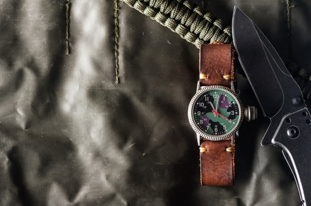 old military or field style of wristwatch with camouflage dial and leather band.