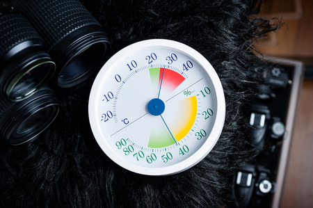 white analog Thermometer and Hygrometer with photography equipments. Lenses and camera equipment are optimally stored at a relative humidity (RH) of around 35% to 45%.