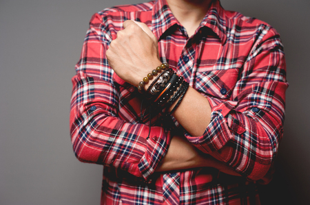 The man in red shirt wearing bracelets, casual style of men accessories. Shallow depth of field.