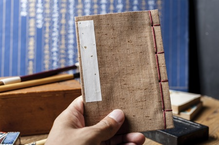 Closeup vintage style of Japanese stab binding in hand. Reading a book.