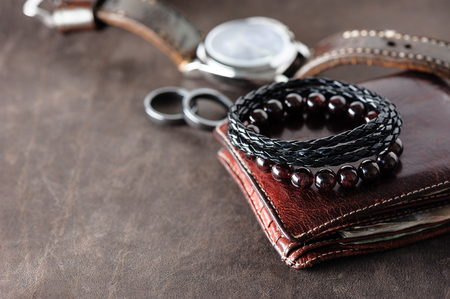 closeup black braided leather bracelet for men, casual style of men accessories. Shallow depth of field.