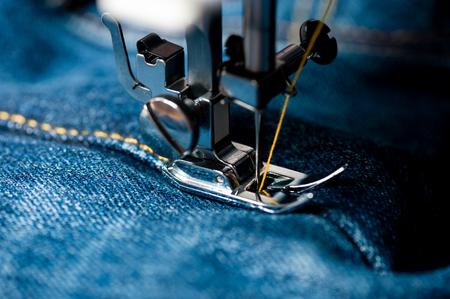 Coser jeans índigo con máquina de coser, concepto industrial de prendas de vestir. Foto de archivo