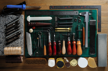 flat lay of leather working tools on wooden desk