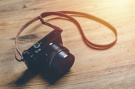 vintage style of digital mirrorless camera with leather strap isolated on wooden background Stock Photo