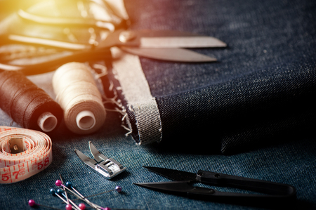 indigo denim fabric with sewing equipments, garment industrial concept.
