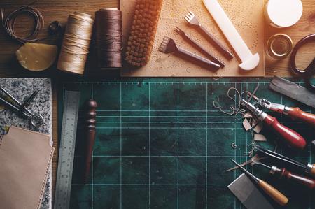 Mise à plat d'outils de travail en cuir sur un bureau en bois Banque d'images