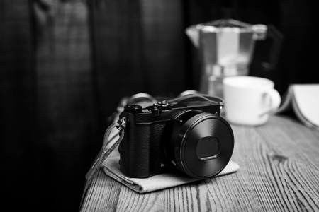 vintage style of digital mirrorless camera with leather strap in black and white Stock Photo