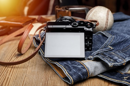 closeup blank screen of digital mirrorless camera with leather strap.