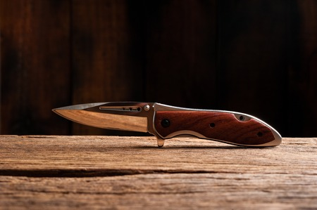 stainless steel folding knife isolated over wood background