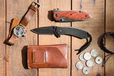 many men's items on wood plank, closeup at stainless steel folding knife. 版權商用圖片