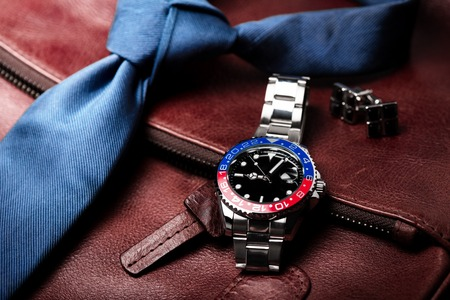 closeup luxury wristwatch for men with black dial blue-red bezel and stainless steel bracelet.